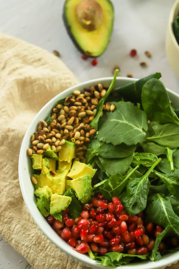 Healthy greens team up with mandarins, pine nuts, avocado, pomegranate seeds, and yummy dressing in this delicious salad!