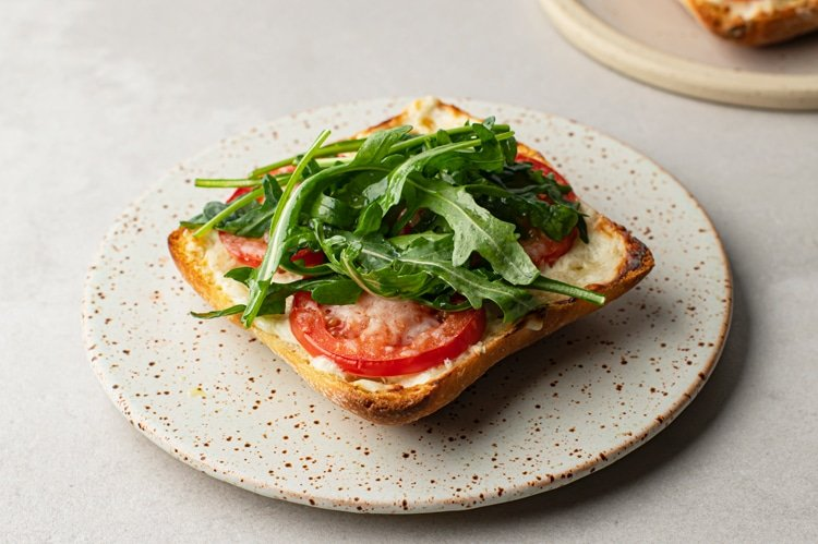 open faced tomato parmesan toast with arugula