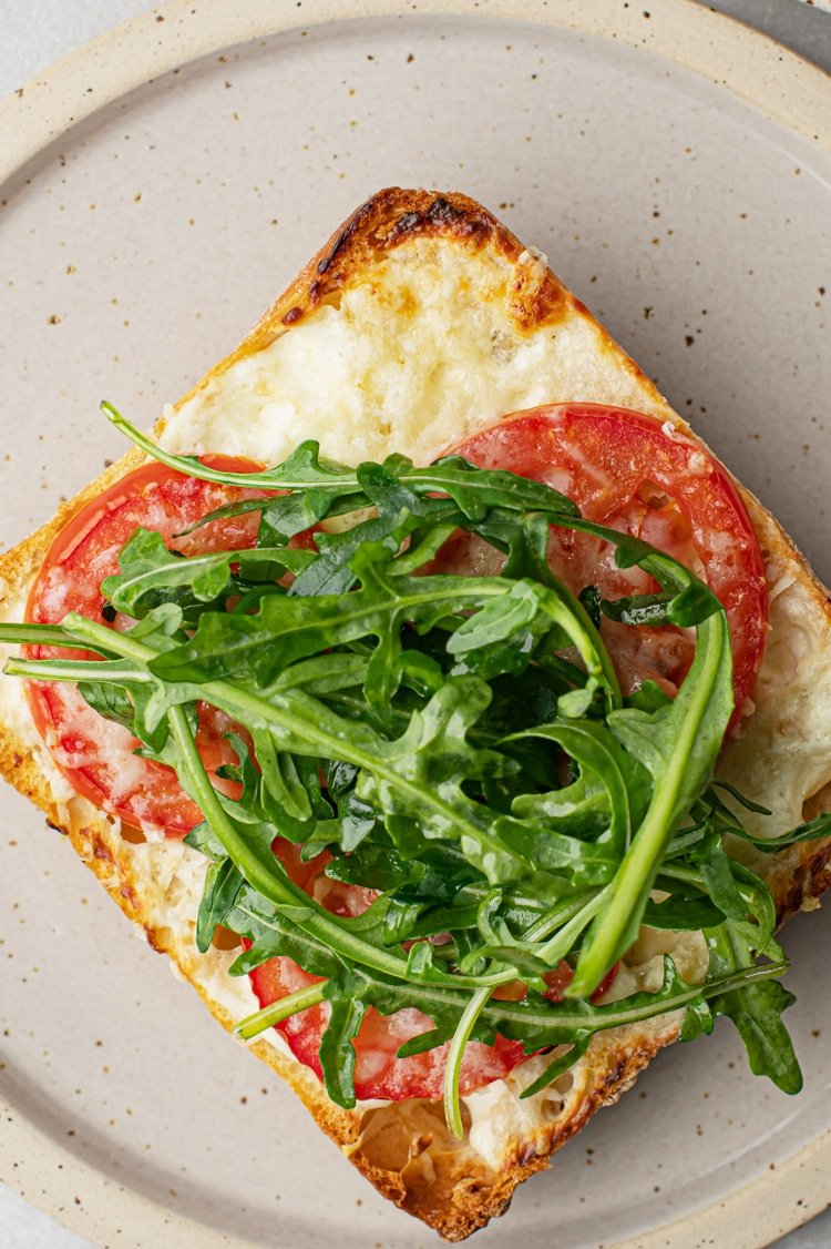 Juicy sweet tomato teams up with Parmesan cheesy deliciousness and bitter arugula, spread gorgeously on delectably crispy ciabatta rolls makes this open-faced toast to die for